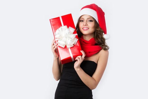 Junges lächelndes mädchen mit geschenken in den händen in einer weihnachtsmannmütze lokalisiert auf weiß