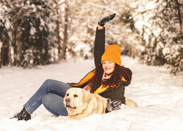 Junges lächelndes mädchen mit weißem hund labrador, der mit schnee im winterwald spielt
