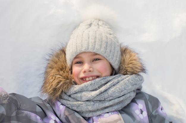 Junges lächelndes mädchen spielt und liegt im schnee
