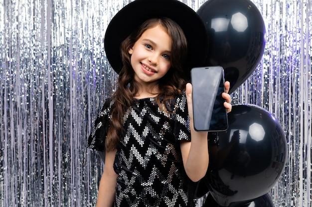Junges lächelndes mädchen zeigt einen telefon-bildschirmschoner mit einem modell auf einer party auf einem glitzernden