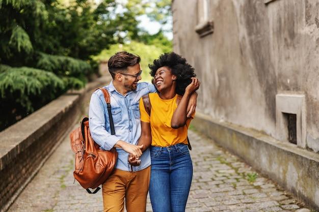 Junges lächelndes niedliches multikulturelles hipsterpaar, das in einer alten stadt geht, umarmt und flirtet.