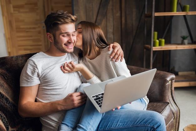 Junges lächelndes paar, das auf couch zu hause im lässigen outfit sitzt