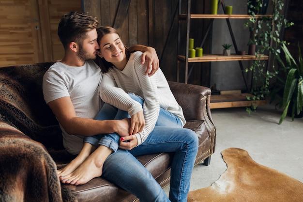 Junges lächelndes paar, das auf couch zu hause in lässigem outfit, liebe und romantik sitzt, frau und mann umarmt, jeans trägt und entspannende zeit zusammen verbringt