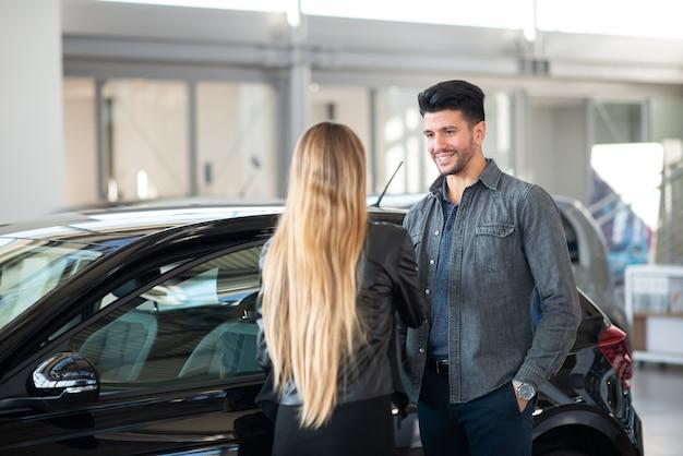 Junges lächelndes paar, das nach einem neuen auto in einem salon sucht