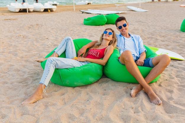 Junges lächelndes paar, das spaß am strand hat, der auf sand mit surfbrettern sitzt