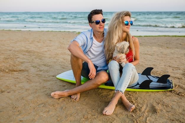 Junges lächelndes paar, das spaß am strand hat, sitzt auf sand mit surfbrettern, die mit hund spielen