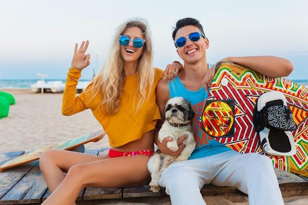 Junges lächelndes paar, das spaß am strand mit drachensurfbrett in den sommerferien hat