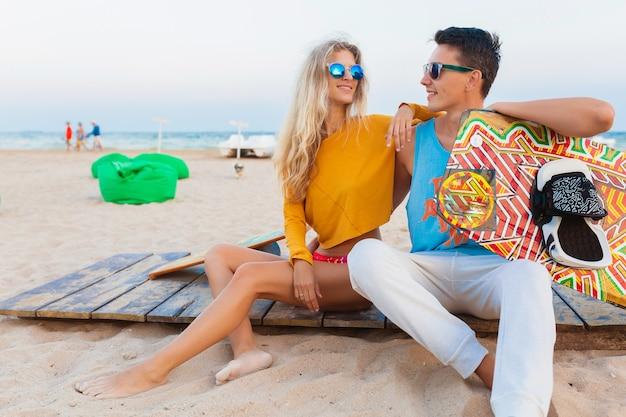 Junges lächelndes paar, das spaß am strand mit kitesurfbrett im sommerurlaub hat?