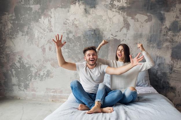 Junges lächelndes paar, das zu hause im lässigen outfit auf bett sitzt, mann und frau, die spaß zusammen haben, verrückte positive emotion, glücklich, hände hochhaltend