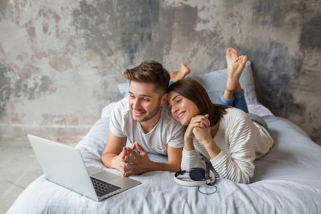 Junges lächelndes paar, das zu hause im lässigen outfit auf dem bett liegt und in laptop, mann und frau schaut, die glückliche zeit zusammen verbringen, entspannend