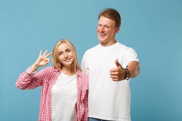 Junges lächelndes paar zwei freund-kerl-mädchen in weißen rosa leeren leeren design-t-shirts posiert