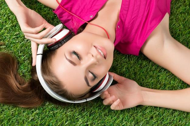 Junges lächelndes schönes mädchen, das auf dem gras im park liegt, der musik hört. sommer- und freizeitkonzept