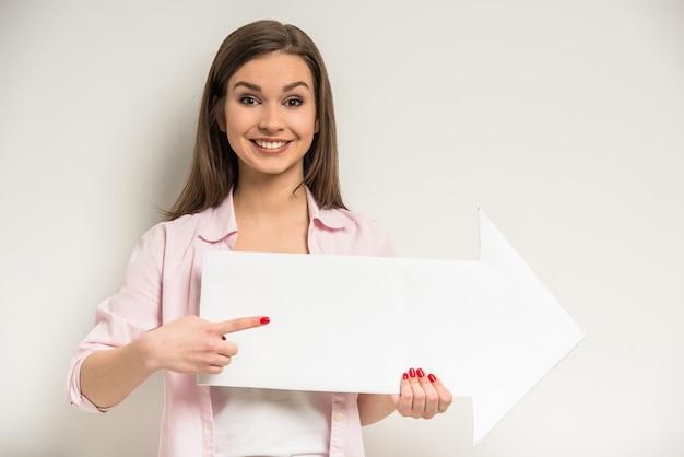 Junges lächelndes schönes mädchen hält leeres papier.