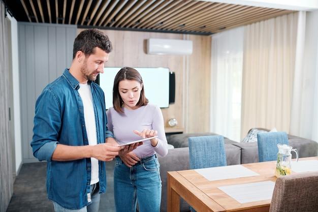 Junges lässiges paar, das neues intelligentes fernsteuerungssystem im digitalen tablett diskutiert, während hübsche frau auf anzeige zeigt