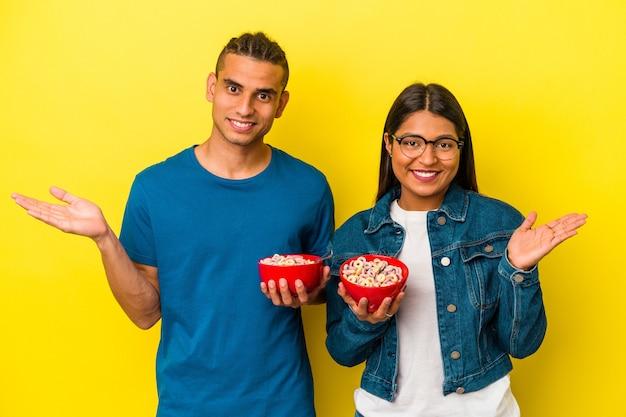 Junges lateinisches paar, das eine getreideschüssel lokalisiert auf gelbem hintergrund hält, der einen kopienraum auf einer handfläche zeigt und eine andere hand auf taille hält.