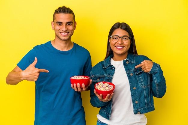 Junges lateinisches paar, das eine müslischale einzeln auf gelbem hintergrund hält, die mit der hand auf einen hemdkopierraum zeigt, stolz und selbstbewusst