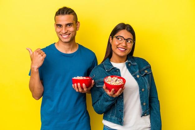 Junges lateinisches paar, das eine müslischale einzeln auf gelbem hintergrund hält, zeigt mit dem daumen weg, lachend und sorglos.
