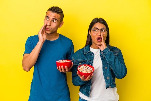 Junges lateinisches paar, das eine müslischale isoliert auf gelbem hintergrund hält, sagt eine geheime heiße bremsnachricht und schaut beiseite