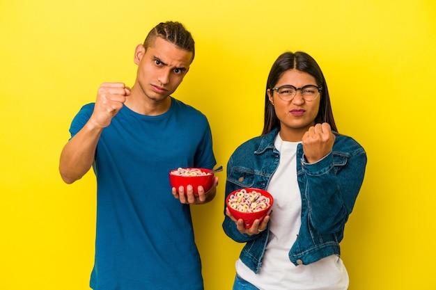 Junges lateinisches paar, das eine müslischale isoliert auf gelbem hintergrund hält und die faust zur kamera zeigt, aggressiver gesichtsausdruck.