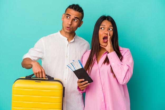 Junges lateinisches paar, das isoliert auf blauem hintergrund reisen wird, sagt eine geheime heiße bremsnachricht und schaut beiseite