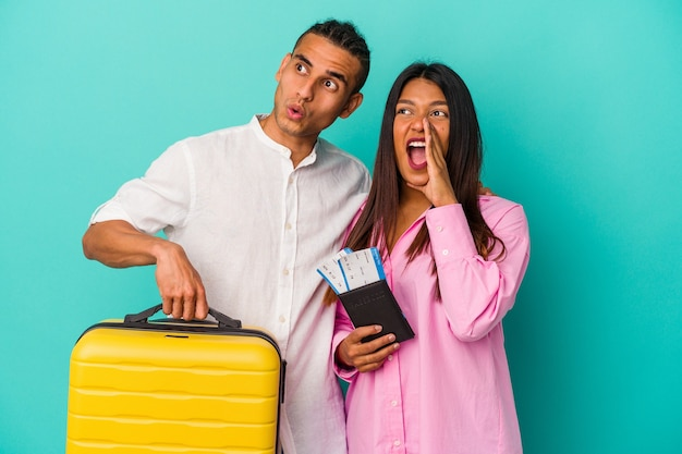 Junges lateinisches paar, das isoliert auf blauem hintergrund reisen wird, schreit und hält palme in der nähe des geöffneten mundes