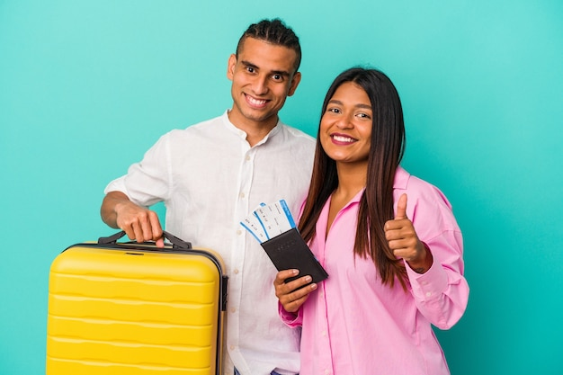 Junges lateinisches paar, das isoliert auf blauer wand reisen wird, lächelt und hebt den daumen hoch