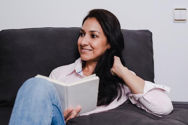Junges latina-mädchen, das ein gutes buch zu hause sitzt auf dem sofa genießt.