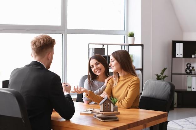 Junges lesbisches paar im büro eines immobilienmaklers
