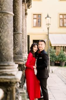 Junges liebendes asiatisches paar gekleidet in luxuskleidung, die nahe alten säulen an der alten stadt im sommer aufwirft
