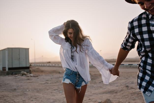 Junges liebendes lachendes paar in den trendigen kleidern, die auf sandhändchenhalten bei sonnenuntergang laufen. lächelnde langhaarige frau im weinlesehemd, die spaß am datum im freien mit ihrem freund im karierten hemd hat