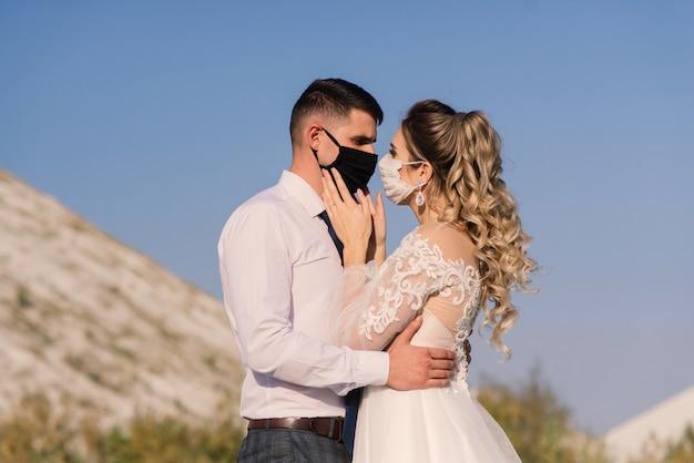 Junges liebendes paar, das in medizinischen masken im park während der quarantäne an ihrem hochzeitstag geht.