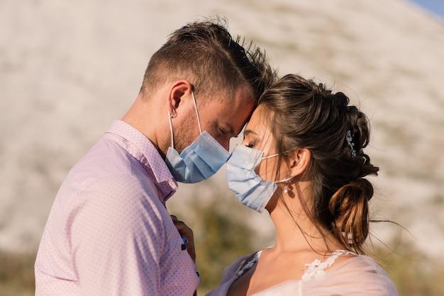 Junges liebendes paar, das in medizinischen masken im park während der quarantäne geht