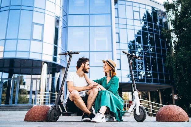 Junges liebendes paar, das sich in der nähe eines modernen glasgebäudes mit ihren elektrorollern entspannt.