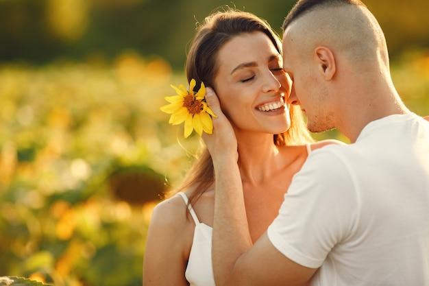 Junges liebendes paar küsst in einem sonnenblumenfeld. porträt des paares, das im sommer im feld aufwirft.