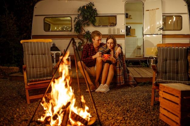 Junges liebespaar, das am lagerfeuer umarmt, picknick auf dem campingplatz im wald