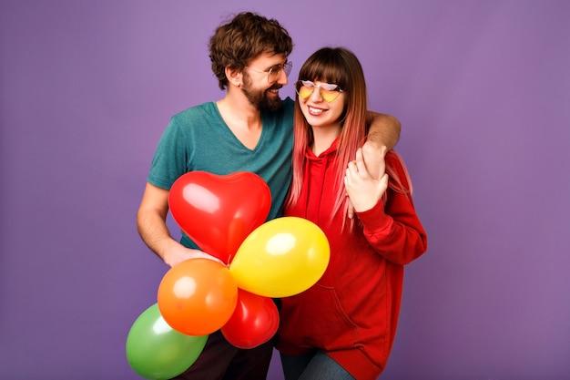 Junges liebespaar, das auf violetter wand mit luftballons aufwirft