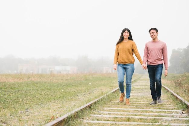 Junges liebespaar, das entlang bahnen geht