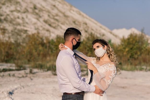 Junges liebespaar, das während der quarantäne an ihrem hochzeitstag in medizinischen masken im park spazieren geht.