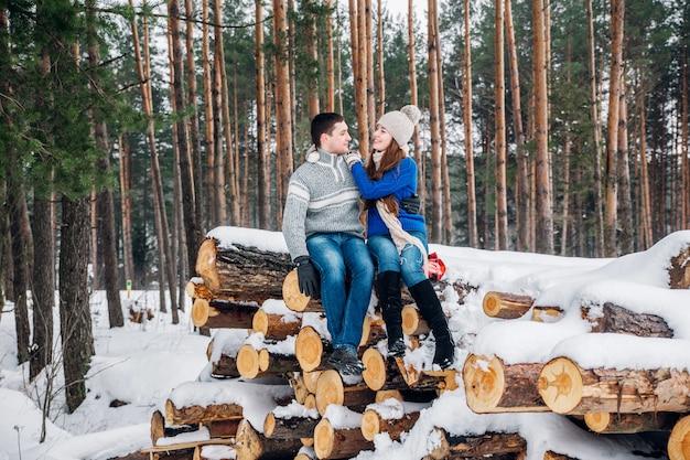 Junges liebespaar kleidete in der blauen strickjacke an, die auf dem brennholz sitzt und im winterwald umarmt