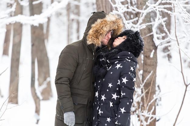 Junges liebespaar küssen in einer verschneiten parkwintersaison