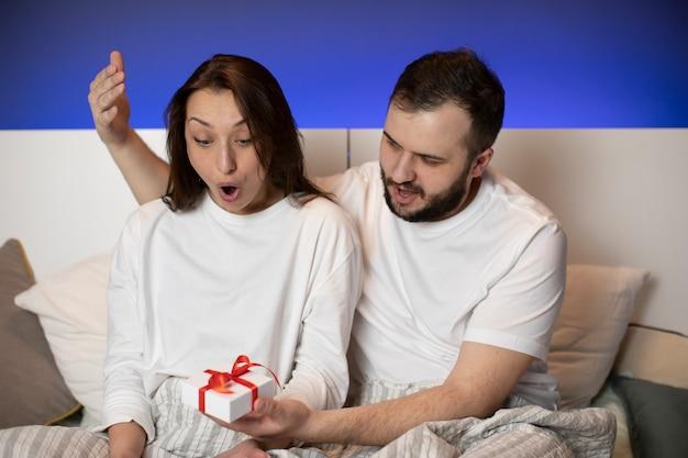 Junges liebespaar sitzt im bett, freund präsentiert geschenkbox zum überraschten mädchen