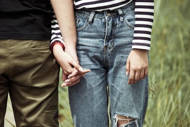 Junges liebespaarhändchenhalten zusammen im weinlesefarbton