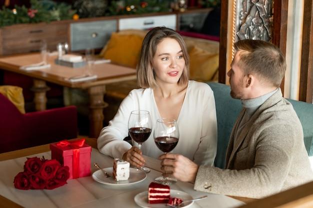 Junges liebevolles paar, das durch dessert und glas rotwein spricht, während es nach dem romantischen mittagessen im restaurant am servierten tisch sitzt