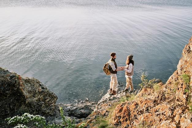 Junges liebevolles romantisches paar, das an den händen hält, während es auf steinfelsen am wasser steht und einander ansieht