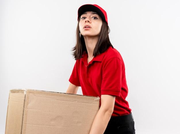Junges liefermädchen, das rote uniform und kappe hält, die großen schweren karton hält, der müde steht, der über weißer wand steht