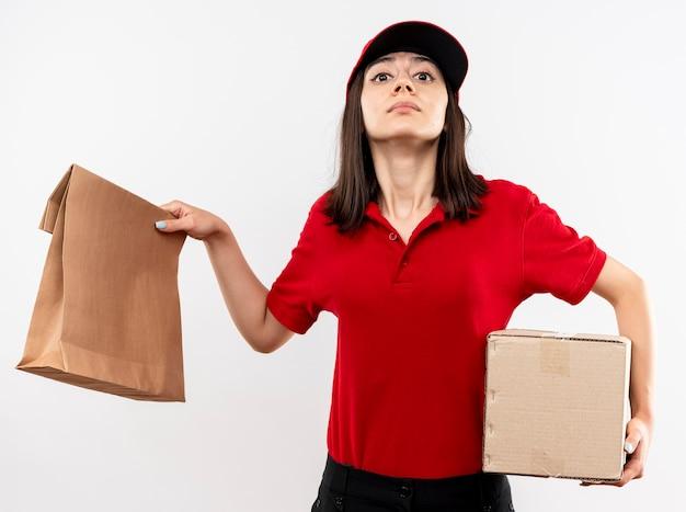 Junges liefermädchen, das rote uniform und kappe hält, die papierpaket und pappkarton betrachten kamera mit sicherem ausdruck, der über weißem hintergrund steht