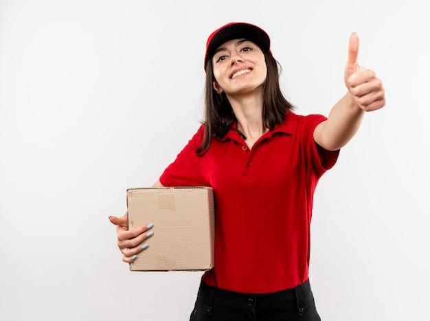 Junges liefermädchen, das rote uniform und kappe hält, die pappkarton lächelnd mit glücklichem gesicht zeigt, das daumen oben steht über weißer wand