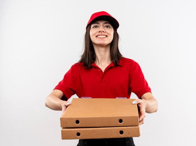 Junges liefermädchen, das rote uniform und kappe hält und pizzaschachteln trägt, die fröhlich über weißer wand stehend lächeln