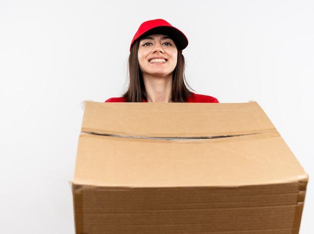 Junges liefermädchen, das rote uniform und kappe trägt, die großen karton mit lächeln auf gesicht hält, das über weißer wand steht