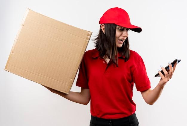 Junges liefermädchen, das rote uniform und kappe trägt, die ihren smartphine-bildschirm hält, der karton hält, der verwirrt über weißer wand steht